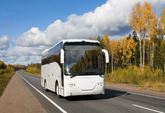 An image of a black and white commercial bus driving on a road after the pre-trip inspection.