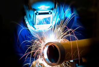 An image of a welding graduate, wearing the proper safety gear while welding a pipe.