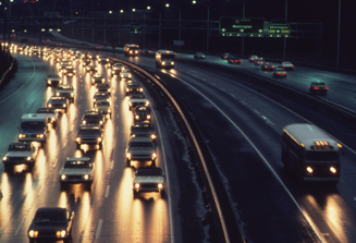 A popular city highway filled with car and bus traffic on a rainy night.