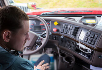 An image of a CDL training student sitting in the driver's seat of a semi truck, looking at the steering wheel and dashboard controls.