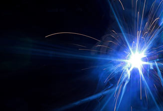 An image of a welder flame emitting blue light on a black background.