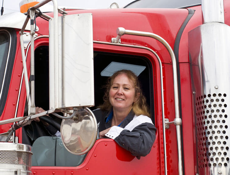 An image of a smiling woman sitting in the driver's seat of her red truck.